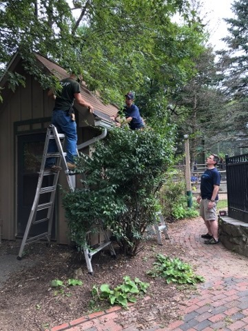 The image features two volunteers, one on a ladder and one on the ground, accompanied by a Zoo employee as they fix the roof on a structure within The Zoo.